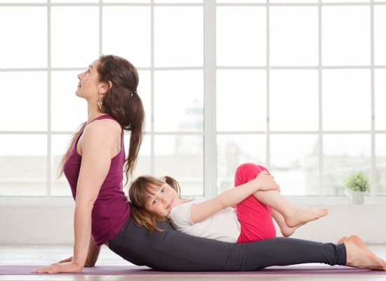 Young mother and daughter doing yoga exercise